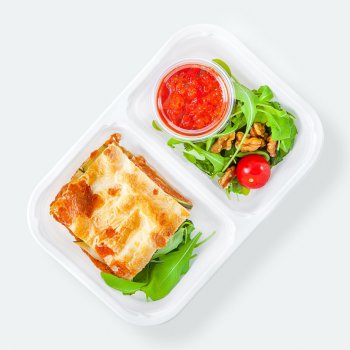 Lasagna with seitan, vegetables and mozzarella, ajvar pepper sauce, rucola